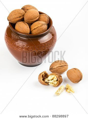 Open Walnuts Closeup In Brown Pot On White Background