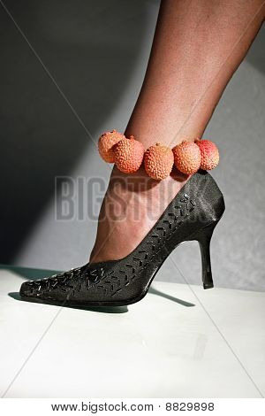 Female foot in a shoe on a high heel and in a bracelet from litchi