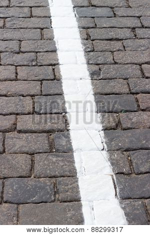 The white line on the road receding the stone