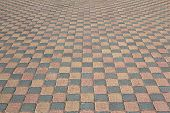 stock photo of paved road  - Orange and gray paving slabs laid out in rows on the road - JPG