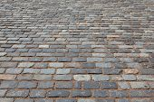 stock photo of paving stone  - Gray paving slabs of natural stone torn lined in rows on the road - JPG