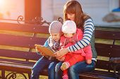 picture of sitting a bench  - Happy family of three - JPG