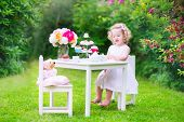 foto of girl toy  - Adorable toddler girl with curly hair wearing a colorful dress on her birthday playing tea party with a teddy bear doll toy dishes cup cakes and muffins in a sunny summer garden