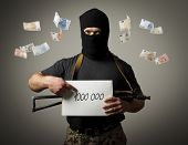 picture of tribute  - Man in mask with gun is holding white paper with a sign - JPG