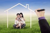 picture of dream home  - Little happy asian family sitting on the meadow while smiling at the camera under a dream home - JPG