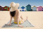 stock photo of beach hut  - Back view of young woman wearing bikini while relaxing at beach and look at the beach huts - JPG