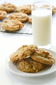 foto of cookie  - Homemade peanut butter cookies with glass of milk and cookies cooling on rack in background - JPG