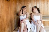 picture of sauna woman  - Young women relaxing on the bench in the sauna - JPG