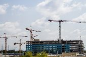 stock photo of construction crane  - Construction site with multiple cranes and running clouds over the construction site - JPG