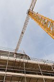 image of tatas  - A view looking up to yellow tower crane on a construction site with concrete and steel structure - JPG