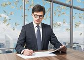 pic of diligent  - Handsome legal consultant is dealing with due diligence process in a modern skyscraper office with a panoramic New York view. Money are falling down from the sky. ** Note: Shallow depth of field - JPG