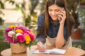 stock photo of flower shop  - Portrait of young female florist talking on phone and making notes at flower shop - JPG