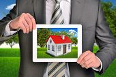 picture of opposites  - Estate agent showing photo with house on tablet screen - JPG