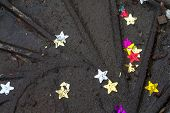 image of manhole  - Coloured stars in dirty water ontop of a dark metal manhole cover - JPG