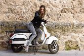 stock photo of vespa  - Woman launching a old scooter with pedal wearing casual clothes in urban background - JPG