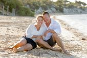 stock photo of couple sitting beach  - young attractive and beautiful American couple in love sitting on the beach the man hugging woman lying on wet sand smiling happy in romantic summer holidays - JPG