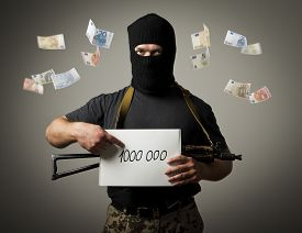 stock photo of tribute  - Man in mask with gun is holding white paper with a sign - JPG