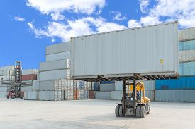 picture of forklift  - forklift handling container box loading to truck in import export logistic zone - JPG