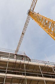 stock photo of tatas  - A view looking up to yellow tower crane on a construction site with concrete and steel structure - JPG