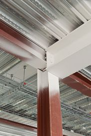 stock photo of tatas  - A view of a spray painted with fire rated paint of a red steel column intersecting a beam on the underside of a standard metal profiled deck - JPG