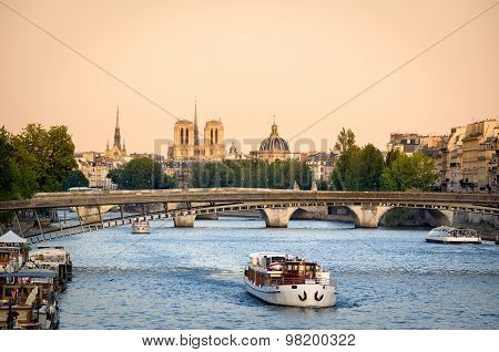 Summer evening light, View of the Seine River in Paris with Passerelle de Solferino bridge and passing tour boat. In the distance are Notre Dame Cathedral the dome of Institut de France and the spire of Sainte Chapelle. Summer evening light.