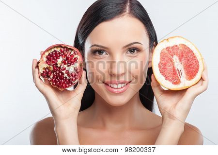 Beautiful young girl is treating with exotic fruits