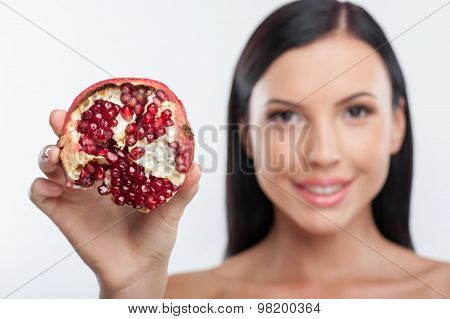 Cheerful young girl is presenting an exotic fruit