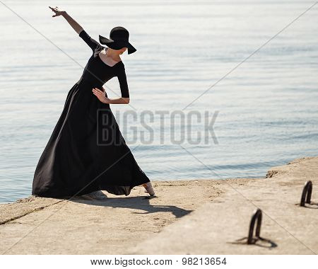 Ballerina In Hat And Black Dress Dancing On The Riverbank.