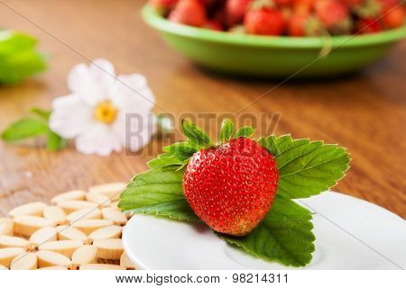 Beautiful juicy strawberry ists and on the plate. With flower and lots of strawberries in the background