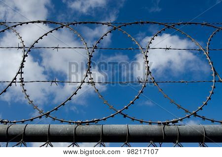 A barbed wire and razor fence against cloudy sky.