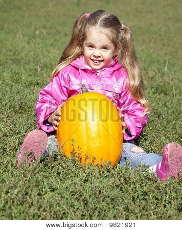 Little gardener girl with pumpkin at green grass