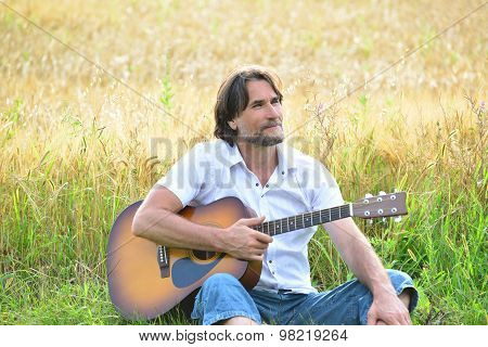 A Man With A Guitar In A Field
