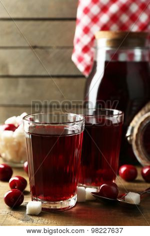 Sweet homemade cherry compote on table on wooden background