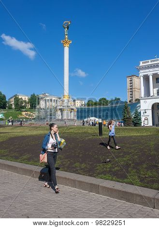Kiev, Ukraine - May 27,2013: Mother And Daughter Walking On The Lawn Talking On The Phone At The Ind