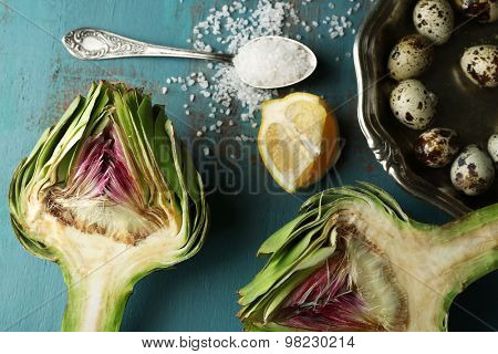 Artichokes, quail eggs and other ingredients on color wooden background