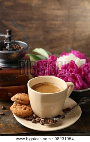 Composition with, coffee grinder, cup of coffee and peony flowers on wooden background