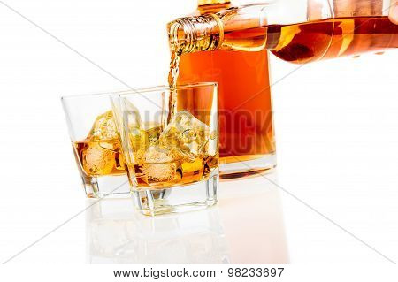 Barman Pouring Whiskey In The Glasses In Front Of Bottle On White Background With Reflection