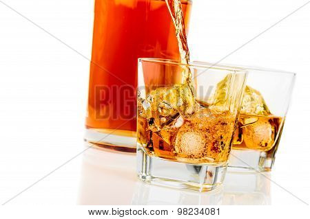 Whiskey In The Glasses In Front Of Bottle On White Background