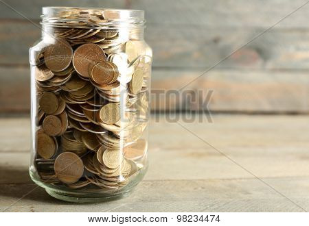 Glass jar with coins on wooden background