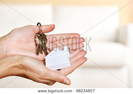 Female hands holding keys with house key chain on blurred sofa background