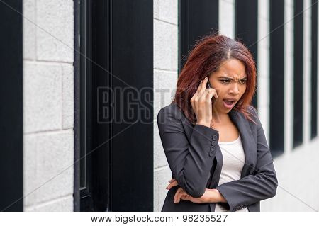 Businesswoman Shocked While Phoning On Mobile Phone