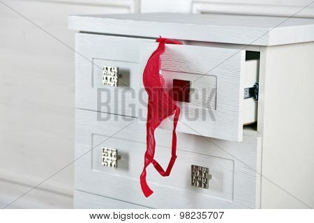 White wooden chest of drawer with bra in opened drawer