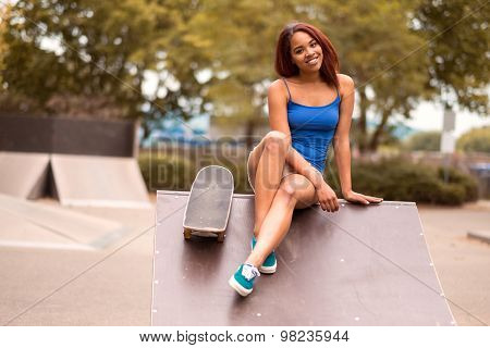 Smiling Sporty Girl With Skateboard Sits On A Ramp