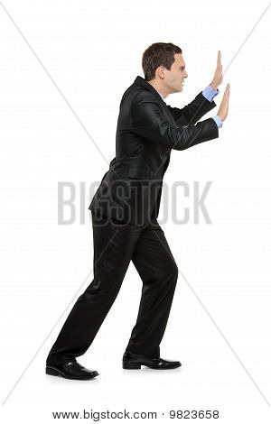 Full Length Portrait Of A Businessman Pushing Something Imaginary