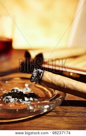 Cigars and burnt one with ash on wooden table, closeup