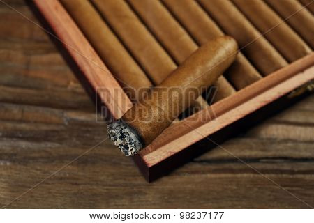 Cigars and burning one in box on wooden table, closeup