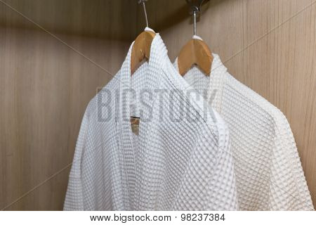 White Bathrobes Hanging In Wooden Closet