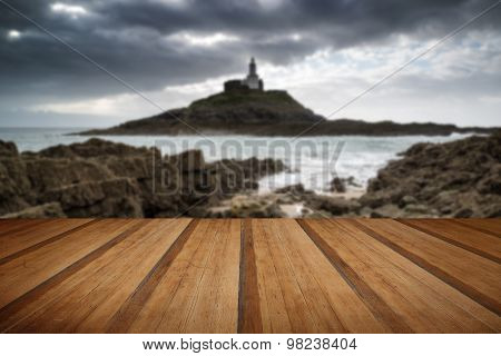 Lighthouse Landscape With Stormy Sky Over Sea With Rocks In Foreground With Wooden Planks Floor