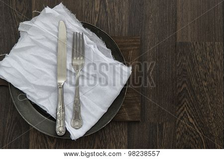 Vintage Cutlery On Muslin Cloth On Pewter Plate With Rustic Dark Wood Backgorund