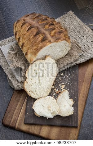 Freshly Baked Rustic Loaf Of Bread In Farmhouse Setting With Wooden Background